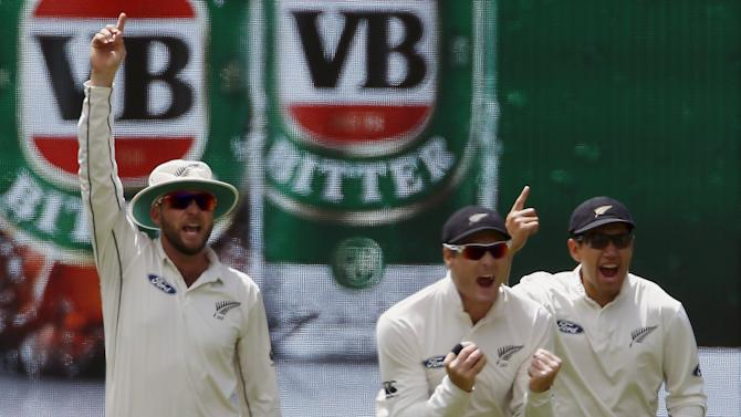 New Zealand's Martin Guptill celebrates with team mates Ross Taylor and Mark Craig after catching Australia's Adam Voges for 13 runs during the second day of the third cricket test match at the Adelaide Oval, in South Australia