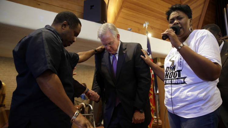"Missouri Gov. Jay Nixon, center, prays during a meeting of clergy and community members held to discuss law enforcement's response to demonstrations over the killing of Michael Brown, Thursday, Aug. 14, 2014, in Florissant, Mo. Nixon says ""operational shifts"" are ahead for law enforcement in the St. Louis suburb where a police officer fatally shot an unarmed black teenager. (AP Photo/Jeff Roberson)"