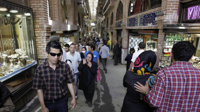 In this picture taken on Saturday, July 14, 2012, Iranians make their way in the main bazaar in Tehran, Iran. Police threatened merchants who closed their shops in Tehran's main bazaar and launched crackdowns on sidewalk money changers on Wednesday, Oct. 3, 2012 as part of a push to halt the plunge of Iran's currency, which has shed more than a third its value in less than a week. (AP Photo/Vahid Salemi)