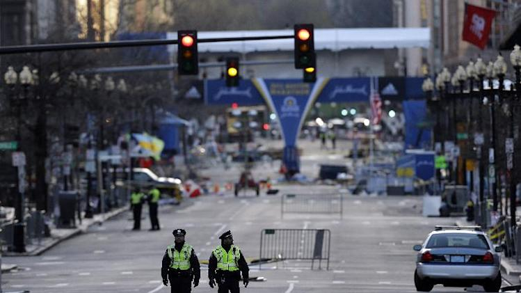 Police officers walk on Boylston Street near the finish line of Monday's Boston Marathon explosions, which killed at least three and injured more than 140, Thursday, April 18, 2013, in Boston. (AP Photo/Matt Rourke)