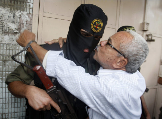 A Gaza man hugs a Palestinian Islamic Jihad militant after a press conference in Gaza City, Thursday, Nov. 22, 2012.  Gazans are celebrating a cease-fire agreement reached with Israel to end eight day