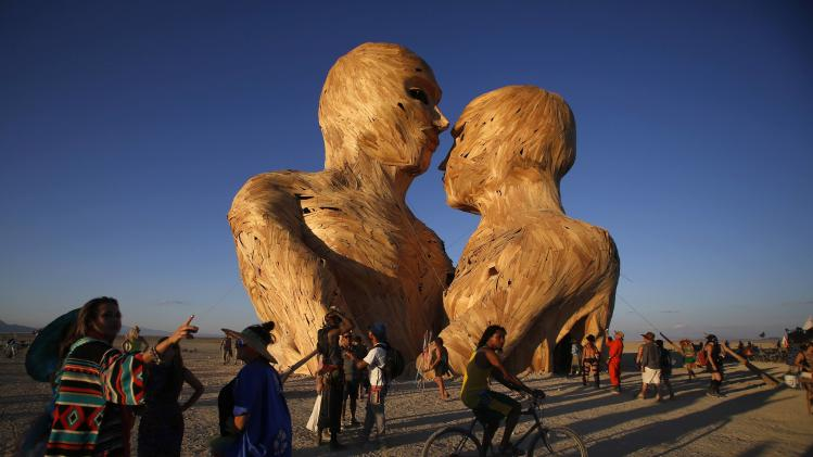 "People gather around the art installation Embrace during the Burning Man 2014 ""Caravansary"" arts and music festival in the Black Rock Desert of Nevada"