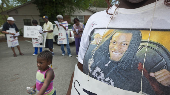 Bree Coleman, right, wears a tee shirt with a picture imprinted on it she says she made of Chavis Carter, in Jonesboro, Ark., as Sakhiya Bell, 4, runs past Tuesday, Aug. 21, 2012. About 20 people marched in protest of the July 28 death of Carter that was ruled a suicide in the back of a Jonesboro Police Department car. (AP Photo/Danny Johnston)
