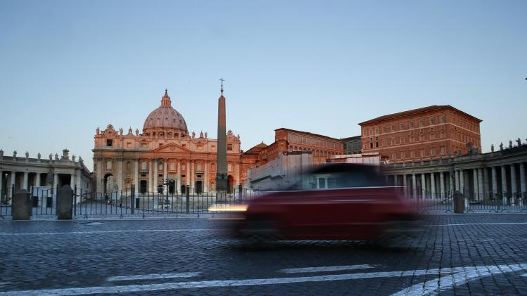 A car drives past Saint Peter's Basilica at the Vatican