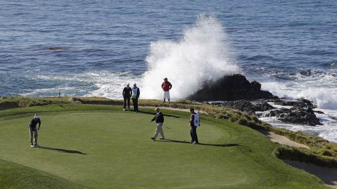 Brandt Snedeker, left, lines up his putt as waves crash behind the seventh green of the Pebble Beach Golf Links during the third round of the AT&T Pebble Beach Pro-Am golf tournament  Saturday, Feb. 9, 2013 in Pebble Beach, Calif. (AP Photo/Eric Risberg)