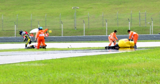 Marco Simoncelli of Italy (58), right,  is seen on the track after the crash at Malaysian MotoGP Grand Prix in Sepang, Malaysia, Sunday, Oct. 23, 2011. A Malaysian MotoGP official says Italian rider M