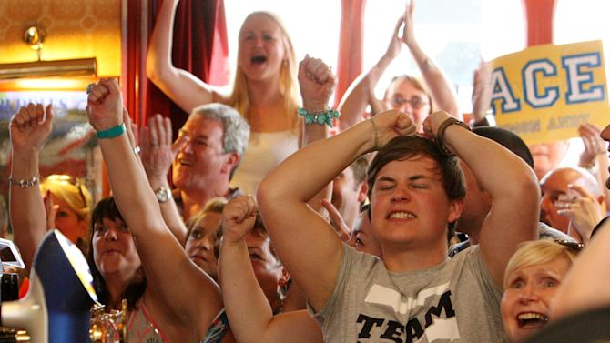 Member's of the public are seen watching tv screens showing Wimbledon tennis final between Andy Murray and Roger Federer in Dunblane, Scotland, Sunday, July 8, 2012. (AP Photo/Scott Heppell)