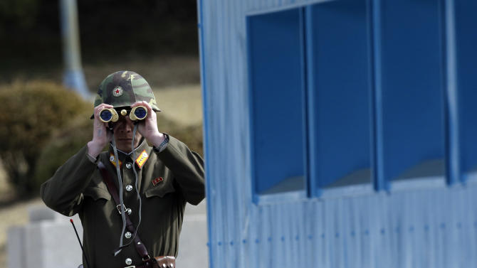 A North Korean soldier looks at the southern side through a pair of binoculars at the border village of the Panmunjom (DMZ) that separates the two Koreas since the Korean War, in Paju, north of Seoul, South Korea, Tuesday, March 19, 2013. The United States is flying nuclear-capable B-52 bombers on training missions over South Korea to highlight Washington's commitment to defend an ally amid rising tensions with North Korea, Pentagon officials said Monday.(AP Photo/Lee Jin-man)