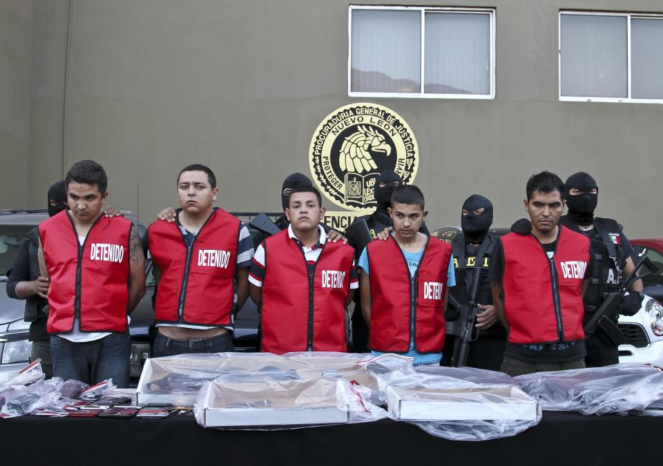Police officers escort five alleged members of the Zetas drug cartel during their presentation to the press in Monterrey, Mexico, Tuesday, Aug. 30 2011. Police arrested five alleged members of the Zetas drug cartel suspected of the arson fire at a casino in Monterrey last Thursday that killed 52 people. (AP Photo/Hans-Maximo Musielik)
