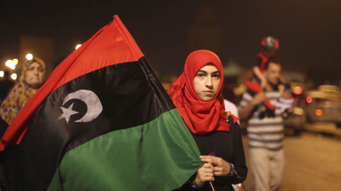 A woman walks on a street carrying a pre-Gadhafi's flag during the celebrations of the capture in Tripoli of his son and one-time heir apparent, Seif al-Islam, at the rebel-held town of Benghazi, Libya, early Monday, Aug. 22, 2011. Libyan rebels raced into Tripoli in a lightning advance Sunday that met little resistance as Moammar Gadhafi's defenders melted away and his 40-year rule appeared to rapidly crumble. The euphoric fighters celebrated with residents of the capital in the city's main square, the symbolic heart of the regime. (AP Photo/Alexandre Meneghini)