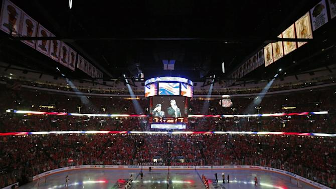 Fans cheer during the performance of the national anthem before Game 1 of the NHL Stanley Cup Final hockey series between the Chicago Blackhawks and the Boston Bruins on Wednesday, June 12, 2013 in Chicago. (AP Photo/Charles Rex Arbogast)