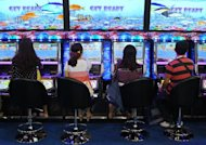Visitors play a game during the G2E Asia gaming expo in Macau on May 23, 2012. The casino industry is booming across Asia, offering anyone looking for high-stakes action a wide choice of venues, from high-tech South Korea to the Himalayan nation of Nepal and communist Vietnam