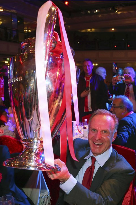 Bayern Munich CEO Karl-Heinz Rummenigge holds up the Champions League trophy at the team's banquet in London