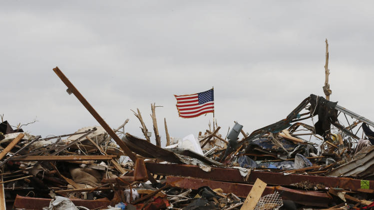 A flag continues to fly amidst the remains of tornado destroyed homes in Moore, Okla., Monday, May 27, 2013. (AP Photo/Sue Ogrocki)