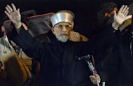 Pakistani religious leader Tahir-ul Qadri greets supporters at a protest rally in Islamabad, on January 15, 2013. The cleric has urged thousands of protesters massed in Islamabad to camp out for another day, defiant after police fired tear gas and the government ignored his ultimatum to disband parliament