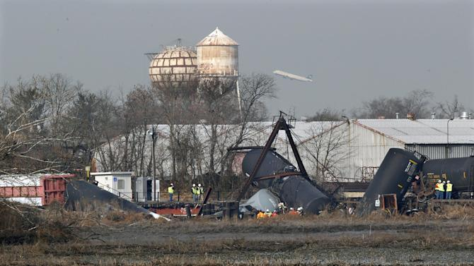 FILE - In this Friday, Nov. 30, 2012 file photo, officials work the scene of derailed freight train tank cars in Paulsboro, N.J. Residents of Paulsboro were ordered to stay inside and schools were closed Monday, Dec. 3, 2012, after unsafe levels of the chemical vinyl chloride were found in the air near where the train derailed last week. (AP Photo/Mel Evans, File)
