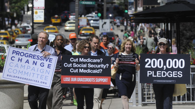 Members of  Progressive Change Campaign Committee upset over potential cuts to Medicare, Medicaid and Social Security walks to  President Obama's campaign headquarters to deliver 200,000 signatures from people who are refusing to donate or volunteer for his re-election campaign if Obama cuts entitlement programs, Friday, July. 15, 2011 in Chicago. (AP Photo/David Banks)