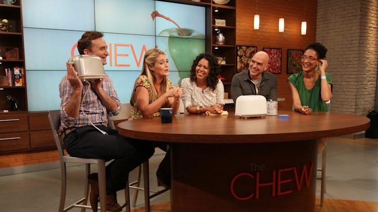 """This Friday, Aug. 26, 2011 photo shows, from left to right, Clinton Kelly, Daphne Oz, Evette Rios, Iron Chef Michael Symon and Carla Hall as they react while Kelly holds up a repainted toaster during a rehearsal of ABC's """"The Chew"""" in New York. Oz, Symon, Hall and Kelly are co-hosts of the show.  Rios is one of the show's correspondents. Can some of food and style TV's biggest stars help ABC soap fans get over cancellation of their favorite stories? The network's counting on it for """"The Chew.""""    (AP Photo/Tina Fineberg)"""