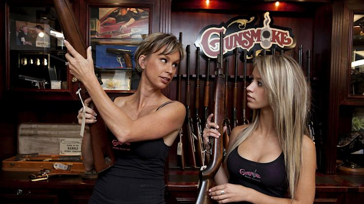 "Renee Wyatt and daughter Paige look at guns in the Gunsmoke store as seen on ""American Guns."""