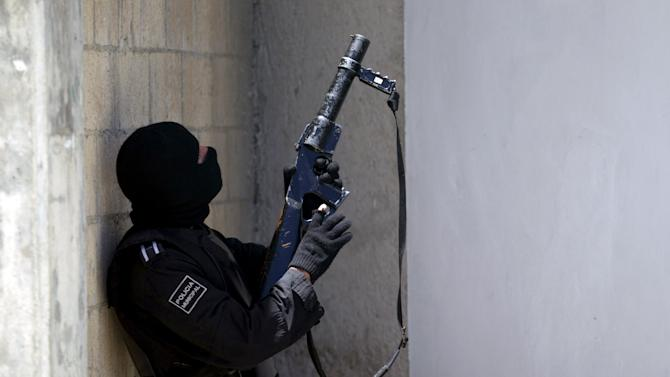 A riot policeman points a tear gas grenade launcher during a clash of rival groups in the jail of Cancun