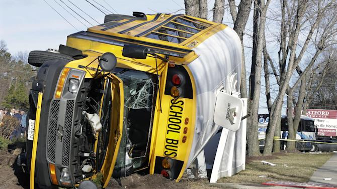 An overturned school bus rests on a fence after colliding with a commuter bus, back right, Thursday, Jan.10, 2013, in Old Bridge, N.J.   School officials said no students were on the Old Bridge school bus, which landed on its side along Route 9. (AP Photo/Mel Evans)