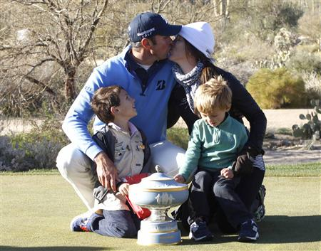Kuchar of the U.S. kisses his wife Sybi as their two sons, Cameron, and Carson watch while posing with the trophy in Marana