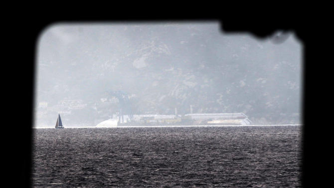 The Costa Concordia cruise ship, seen through a ferry window, leans on its side of the Tuscan Island Isola del Giglio, Italy, Saturday, Jan. 12, 2013. More time and money will be needed to remove the Costa Concordia cruise ship from the rocks off Tuscany where it capsized last year, in part to ensure the toxic materials still trapped inside don't leak into the marine sanctuary when it is righted, officials said Saturday. On the eve of the first anniversary of the grounding, environmental and salvage experts gave an update on the unprecedented removal project under way, stressing the massive size of the ship — 112,000 tons, its precarious perch on the rocks off the port of Giglio island and the environmental concerns at play.  (AP Photo/Gregorio Borgia)