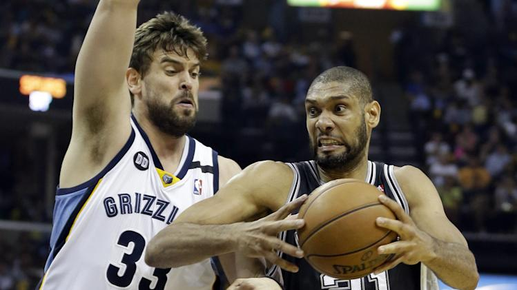 San Antonio Spurs forward Tim Duncan (21) drives to the basket as Memphis Grizzlies center Marc Gasol (33) defends, during Game 4 of the Western Conference finals NBA basketball playoff series in Memphis, Tenn., Monday, May 27, 2013. The Spurs defeated the Grizzlies 93-86 to advance to the NBA finals. (AP Photo/Danny Johnston)