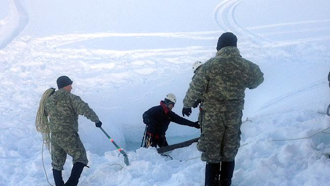 In this photo provided by the U.S. Army and made Sunday April 14, 2013, members of the Army's Alaska Northern Warfare Training Center prepare to descend 145 feet to a 15-foot space inside an Alaska glacier in the Hoodoo Mountains to extract the body of a 9-year-old boy who fell through the hole on his snowmobile on Saturday. The men on Sunday shoveled 3,000 pounds of snow into bags lifted out by soldiers at the surface to reach the body of Shjon Brown. (AP Photo/U.S. Army)