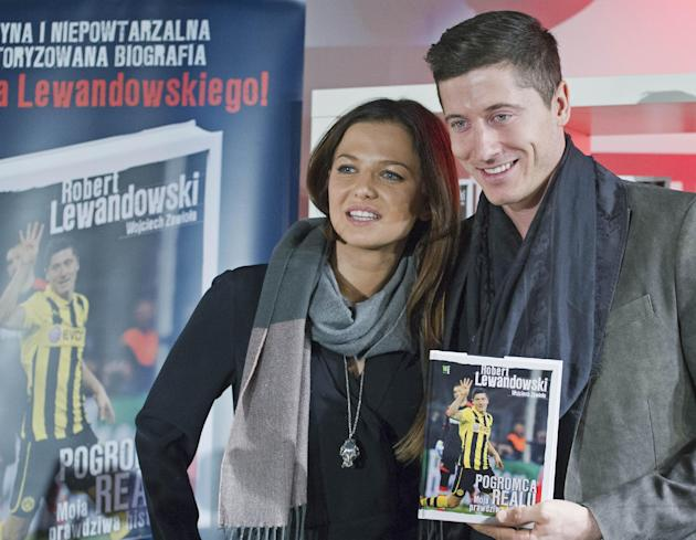 "Borussia Dortmund's striker Robert Lewandowski from Poland holds his biography book entitled ""Robert Lewandowski.  The Man Who Defeated Real. My True Story""  as he poses with his wife An"