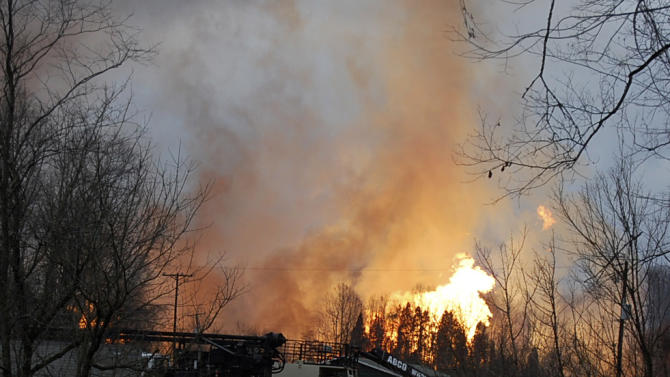Flames are seen from a gas line explosion across Interstate 77 near Sissonville, W.Va., Tuesday, Dec. 11, 2012. West Virginia State Police say several structures are on fire and about a mile of Interstate 77 is shut down in both directions.  (AP Photo/Joe Long) MAGS OUT