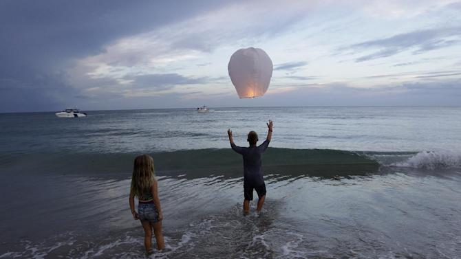 Andrew Grubowski, 10, of Palm City, Fla., releases a lantern during a vigil for Austin Stephanos and Perry Cohen, Tuesday, July 28, 2015, in Stuart, Fla. The two teenagers have been missing since last Friday when they went out on a boat to go fishing from Tequesta, Fla. A search continues for the boys from the Atlantic waters off Daytona Beach, Fla, north through Savannah, Ga. (AP Photo/Lynne Sladky)