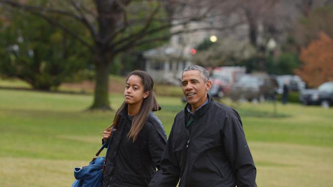 US President Barack Obama (R) and daughter Malia make their way across the South Lawn upon returning to the White House on January 4, 2015 in Washington, DC