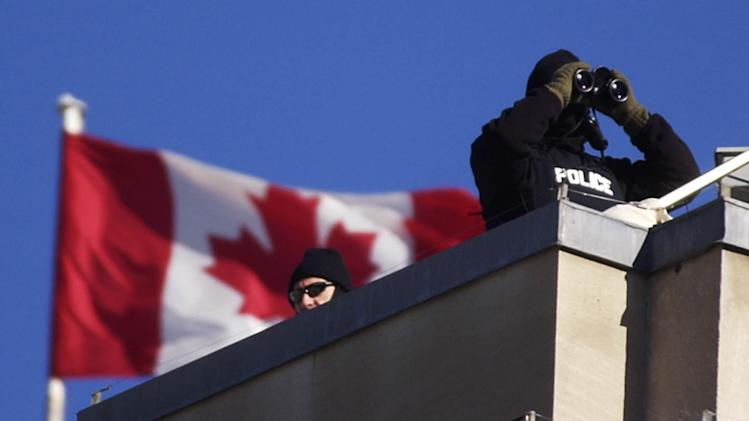 Royal Canadian Mounted Police team keep watch from the roof of the Government Conference Center in Ottawa