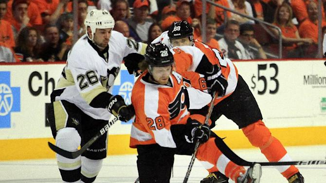Pittsburgh Penguins Steve Sullivan, left, knocks Philadelphia Flyers Claude Giroux off the puck in the neutral zone as Jaromir Jagr, rear, trails during the second period of Game 3 in a first-round NHL Stanley Cup playoffs hockey series, Sunday, April 15, 2012, in Philadelphia. (AP Photo/Tom Mihalek)