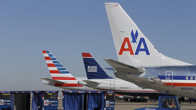 U.S. Airways and American Airlines planes are shown at gates at DFW International Airport Thursday, Feb. 14, 2013, in Grapevine, Texas. The two airlines will merge forming the world's largest airlines.  (AP Photo/LM Otero)