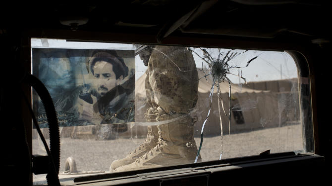 In this Friday, Oct. 19, 2012 photo, a member Afghanistan's elite Civil Order Police stands next to a bullet damaged windsheild of his armored vehicle after coming back from a patrol in Marjah, southern Helmand province, Afghanistan. The window is decorated with a picture of Afghanistan's famed anti-Taliban warrior Ahmed Shah Masood. As the U.S. and NATO close out their mission in Afghanistan preparing for the final withdrawal of combat troops by the end of 2014, the worry looms large that fresh outbursts of ethnically motivated fighting would send the country into a spiral of chaos and violence. (AP Photo/Anja Niedringhaus)