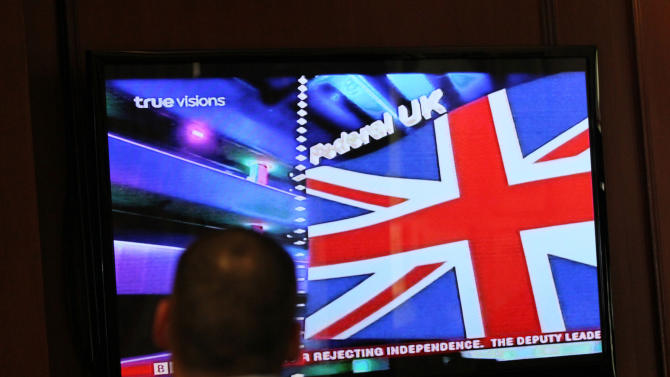 A Briton living in Thailand watches a TV reporting Scotland's referendum results at the Churchill Bar in Bangkok, Thailand, Friday, Sept. 19, 2014. Scottish voters rejected independence, deciding to remain part of the United Kingdom after a historic referendum that shook the country to its core. (AP Photo/Sakchai Lalit)
