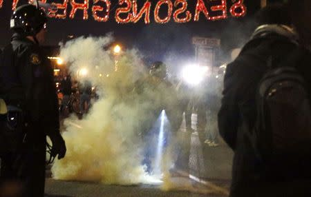 A police officer is engulfed in smoke from a device thrown into the police line by protesters in Ferguson