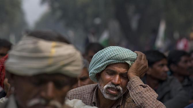 Indian farmer Ghaliapita Hara, 45, holds his head as he listens to a speaker during a protest against the government's proposed move to ease rules for acquiring land to facilitate infrastructure projects, in New Delhi, India, Wednesday, Feb. 25, 2015. Hara, who is from Indian state of Madhya Pradesh, said that his land was taken away by an industrial group and he was not duly compensated by the government. (AP Photo/Manish Swarup)