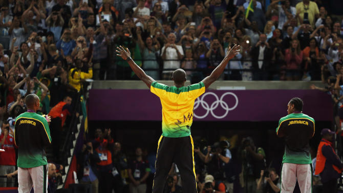 Jamaica's Usain Bolt, center, celebrates before receiving his gold medal as he stands alongside silver medallist Yohan Blake of Jamaica, right, and bronze medallist Warren Weir of Jamaica during the medal ceremony for the men's 200-meter during the athletics in the Olympic Stadium at the 2012 Summer Olympics, London, Thursday, Aug. 9, 2012. (AP Photo/Matt Dunham)