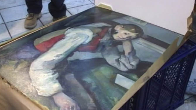 """A Serbian police display the masterpiece by French impressionist Paul Cezanne, """"The Boy in the Red Vest"""" which they discovered in a vehicle  in Belgrade Thursday April 12, 2012 in this image taken from video released by the Serbian Interior Ministry.  The masterpiece by French impressionist Paul Cezanne, """"The Boy in the Red Vest""""  which was stolen from a private Swiss museum in 2008 in one of the biggest art thefts in Europe,was discovered in Serbia, police said Thursday. Serbian police went on to say three people were arrested in connection with the robbery.(AP Photo/Serbian Interior Ministry/AP Video) TV OUT"""
