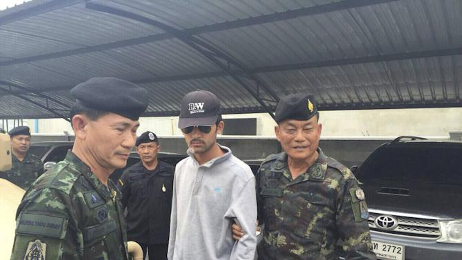 Royal Thai Army officers walk with a suspect, believed to be involved in the recent Bankgkok blast, after his arrest in Sa Kaeo