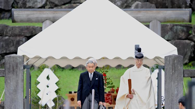 FILE - In this June 22, 2009 file photo, Japanese Emperor Akihito, center, is led by a Shinto priest when he visits the tomb of his late father Emperor Hirohito at the Musashino Mausoleum in Hachioji in the western suburbs of Tokyo. Akihito, turning 80 on Monday, Dec. 23, 2013 is still active, making an official visit to India in November with his wife, the 79-year-old Empress Michiko. But concerns have grown since he had heart bypass surgery nearly two years ago on top of prostate cancer earlier. After an expert panel discussion for more than a year, the palace announced that Akihito will be cremated, and his remains placed in a mausoleum smaller than those of his predecessors, with Michiko's by his side at the Imperial compound in western Tokyo. Akihito's cremation breaks a 400-year burial custom of the world's oldest monarchy, as he wishes to trim cost, space and burden on the people, officials said. (AP Photo/Toru Yamanaka, Pool, File)