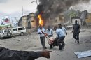 Somali security force members carry away a wounded civilian following a suicide car bomb blast in the capital Mogadishu, Somalia Sunday, May 5, 2013. A Somali police official at the scene said four civilians and a soldier were killed after the suicide bomber attempted to ram a car laden with explosives into a military convoy. (AP Photo/Farah Abdi Warsameh)