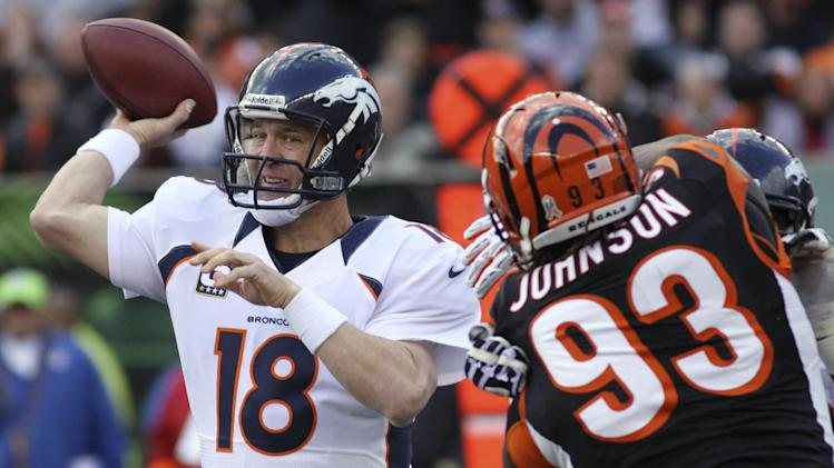 Denver Broncos quarterback Peyton Manning (18) passes under pressure from Cincinnati Bengals defensive end Michael Johnson (93) during the first half of an NFL football game, Sunday, Nov. 4, 2012, in Cincinnati. (AP Photo/Tom Uhlman)