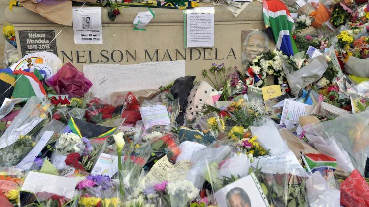 Flowers and tributes lay at the foot of a statue of former South African President Nelson Mandela in Parliament Square in central London