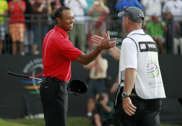 Woods celebrates with his caddie Joe LaCava after sinking his final putt on the 18th green to win the 2013 WGC-Cadillac Championship PGA golf tournament in Doral