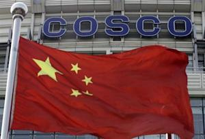 A Chinese national flag flies in front of COSCO's headquarters in Beijing