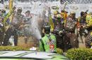 Kyle Busch sprays his crew after winning the NASCAR Sprint Cup Series auto race Sunday, June 28, 2015, in Sonoma, Calif. (AP Photo/Eric Risberg)